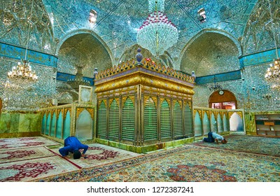 YAZD, IRAN - OCTOBER 18, 2017: The shia muslims pray in shrine of Imamzadeh Jafar, richly decorated with complex patterns of shining mirror pieces, on October 18 in Yazd.