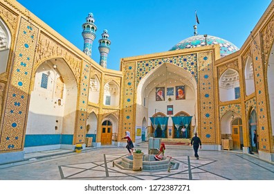 YAZD, IRAN - OCTOBER 18, 2017: Courtyard of Imam Zadeh Jafar Shrine with ablution fountain, walls, dome and minarets in  Islamic patterns of tile and stucco muqarnas in niches, on October 18 in Yazd.