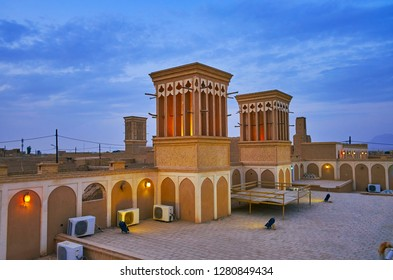 YAZD, IRAN - OCTOBER 18, 2017: The evening sky over the medieval badgirs (windcatchers) of Tehraniha (Fahadan) House - historic mansion, serving as hotel in old town, on October 18 in Yazd.