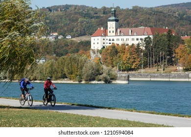 YBBS AN DER DONAU, AUSTRIA - OCTOBER 14, 2018. Middle-aged couple riding bicycles along the Danube river on the famous cycling route Donauradweg. View of the Persenbeug castle. Lower Austria, Europe.