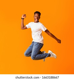 Yeah. Excited screaming african man jumping while celebrating his victory or triumph over orange background