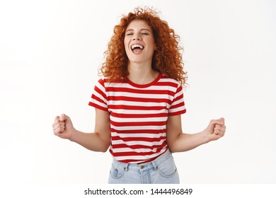 Yeah feeling freedom women power. Attractive carefree lively redhead curly woman enjoy having fun release emotions dancing close eyes scream yes thrilled clench fists triumphing winning lottery