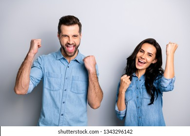 Yeah! Hooray! Portrait of yelling excited person students delighted impressed about their luck in lottery raising fists wearing blue denim clothing isolated on argent background