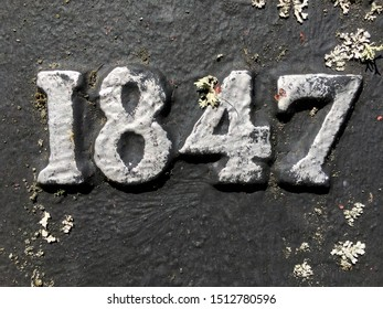 The year 1847 in cast iron taken from an inscription produced that year. Painted in silver on a black background. Covered with lichen