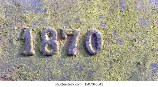 The year 1870 taken from a cast-iron inscription painted in black and covered with lichen. Produced at the same time