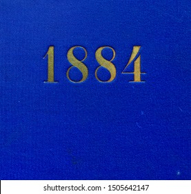 The year 1884 printed in gold on the blue cloth binding of a yearbook published that year