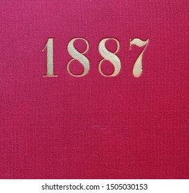 The year 1887 printed in gold on the red cloth binding of a yearbook published that year