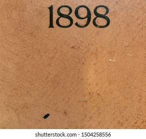 The year 1898 printed in black on the brown binding of a yearbook published that year