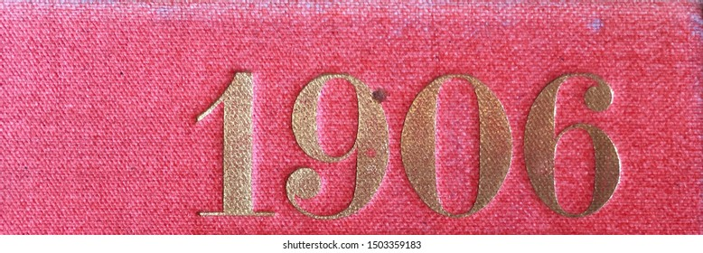 The year 1906 printed in gold on the red cloth binding of a yearbook published that year