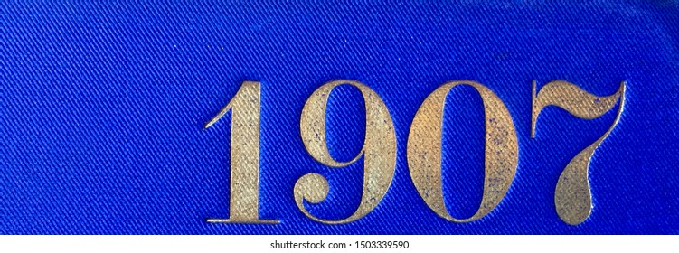 The year 1907 printed in gold on the blue cloth binding of a yearbook published that year