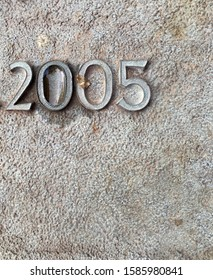 The year 2005 cast in metal and affixed to a stone, seen on a rainy day – a detail of an inscription produced that year