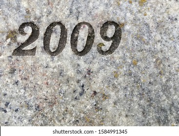 The year 2009 carved in stone and painted in black. Covered with lichen