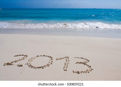 Year 2013 hand written on the white sand in front of the sea