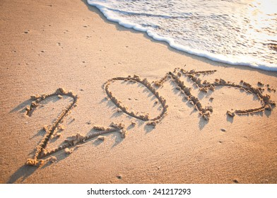 Year 2015 written by hand on the sand with wave
