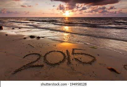 Year 2015 written on sand at sunset