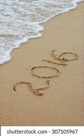 Year 2016 written in sand on a sea beach.