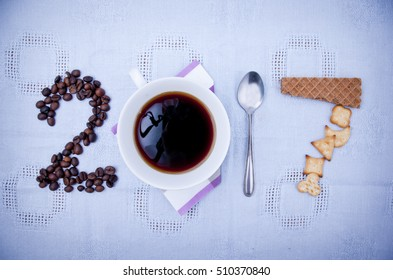 Year 2017 shape made of coffee beans, cup of coffee, spoon and biscuits, concept.