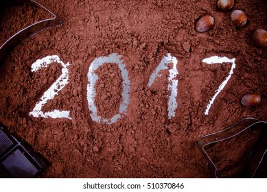 Year 2017 written in cocoa powder decorated with chocolate, nuts and casts.