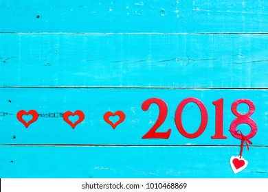 Year 2018 in bold red by red hearts border on antique rustic teal blue wood background; message board or sign with Valentines Day holiday and love concept and painted copy space