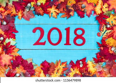 Year 2018 in bold red and colorful autumn leaves border with butterfly hanging on antique rustic teal blue wood background;  seasonal sign
