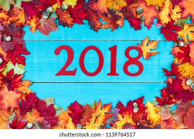 Year 2018 in bold red and colorful autumn leaves border hanging on antique rustic teal blue wood background;  seasonal sign