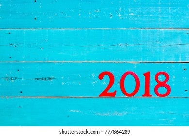 Year 2018 in bold red on blank antique rustic teal blue wood background; message board with New Year holiday concept and painted copy space