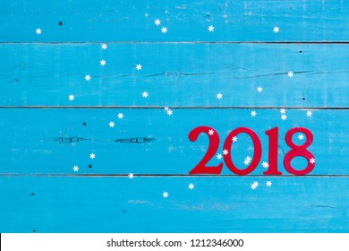 Year 2018 numbers in red with holiday winter snowflakes on antique rustic teal blue wood background; seasonal blank sign with painted copy space