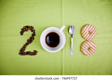 Year 2018 shape made of coffee beans, cup of coffee, spoon and cookies on green backgound, concept.