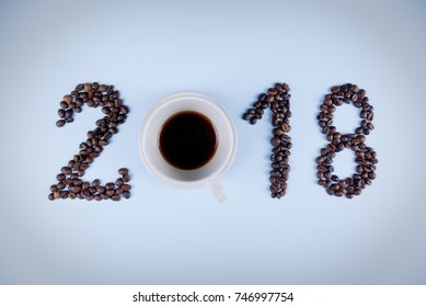 Year 2018 shape made of coffee beans and cup of coffee on light blue background, concept.
