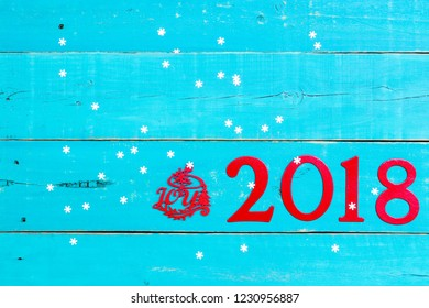 Year 2018 and the word Joy in bold red on blank antique rustic teal blue wood background with snowflakes; message board with Christmas holiday concept and painted copy space