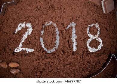 Year 2018 written in cocoa powder decorated with chocolate, nuts and casts.