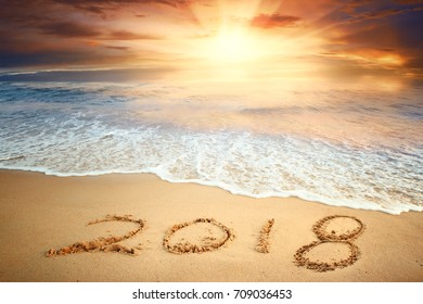 Year 2018 written on sand at sunrise