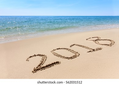 Year 2018 written at the sand beach with sea wave water