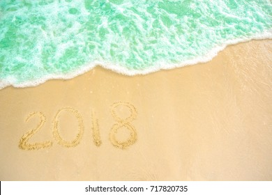 Year 2018 written at the sand beach with sea wave water. wave coming to 2018 concept on the sand beach in the morning.Text 2018 on a beach sand. Concept New Year 2018 is coming soon