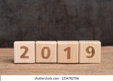 Year 2019 begin concept, simple and minimal cube wooden block building number of year 2019 on wood table with dark blackboard background with copy space.