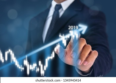 year 2019 business man point hand on the top of arrow graph with high rate of growth. The success and growing growth graph in the company or industrial after investment and preparing for year 2020