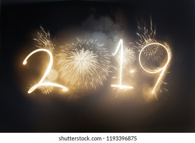 The year 2019 displayed with gold sparkling fireworks and strobes. New year celebration concept.
