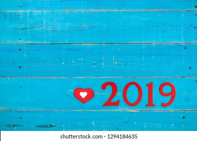 Year 2019 and heart in bold red on blank antique rustic teal blue wood background; message board with Valentine's Day holiday concept and painted copy space