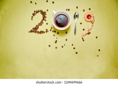 Year 2019 numbers made of coffee beans, cup od coffee, spoon and cookies. New year concept.