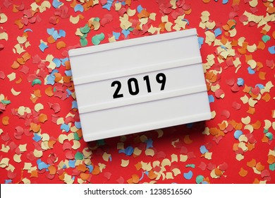 year 2019 - numbers on lightbox sign on red paper background with confetti - new years eve party celebration concept flat lay with copy space