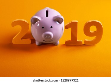 Year 2019, smiling pink piggy bank with wooden number 2019 on yellow table.