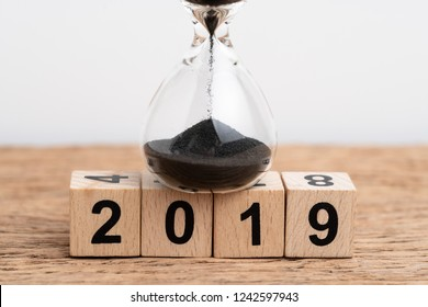 Year 2019 time running or countdown concept, Closed up of sand dropping in hourglass or sandglass on stack of cube wooden block building year number 2019 on wood table with white background.