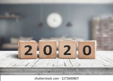 Year 2020 sign on a wooden desk in a cozy kitchen with a blurry background