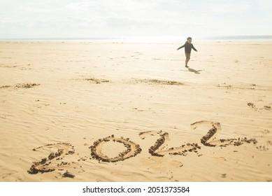 Année 2022 écrite dans le sable d'une plage. Un enfant court joyeusement à l'arrière-plan.