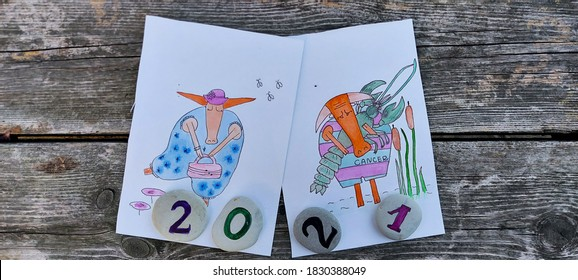 Year of the bull 2021. Two bulls, virgo zodiac signs in a dress and hat and cancer with a lobster in its paws. Against the background of a wooden surface.