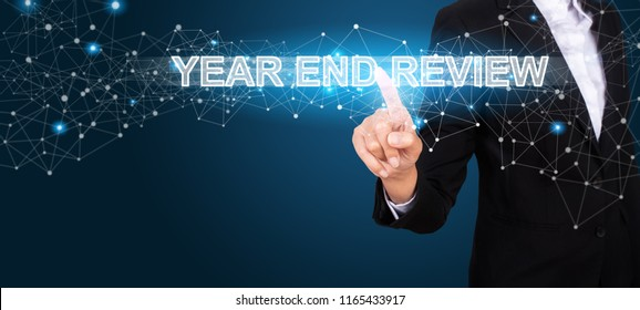 Year End Review concept with Hand of business pressing a button Year End Review.
