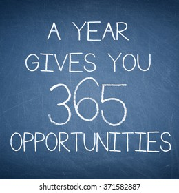 A YEAR GIVES YOU 365 OPPORTUNITIES motivational quote written on a blue blackboard