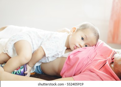 A year old Asian baby Breastfeeding by his mother
