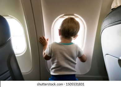 A year old baby boy curiously looking through airplain's window