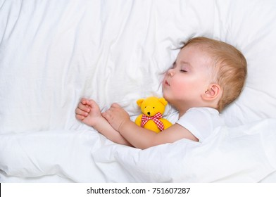 Year old child sleeps in a white bed with her favorite toy his bear